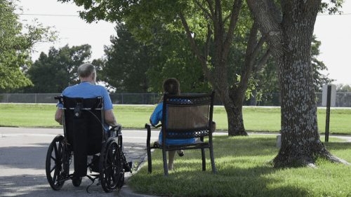 Photo of people sitting outside a nursing home.