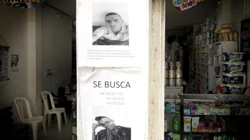 Posters requesting information on the whereabouts of two disappeared men on the wall of a store in the city of Tumaco, August 9, 2018.