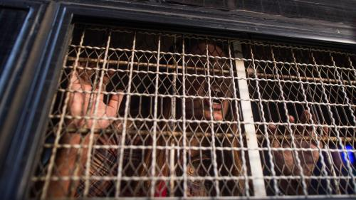 A demonstrator shouts from inside a prison van after being detained by Myanmar police during an anti-war protest in Yangon, May 12, 2018.