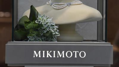 "A pearl necklace is displayed over a gray sign that reads ""Mikimoto"""