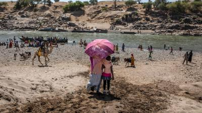 Refugees who fled the conflict in Ethiopia's Tigray region, which involved Eritrean as well as Ethiopian forces, arrive on the banks of the Tekeze River on the Sudan-Ethiopia border, November 20, 2020.