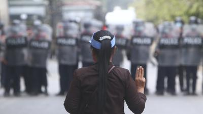 A protester flashes the three-fingered salute in front of police in Mandalay, Myanmar, February 20, 2021.