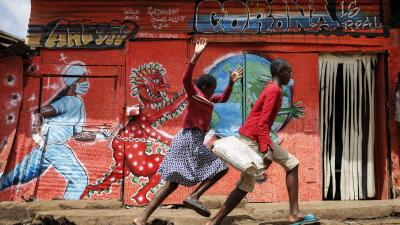 Children run past a mural that warns people about the dangers of the new coronavirus, in the Kibera informal settlement of Nairobi, Kenya.