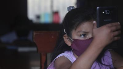 A young girl wearing a face mask holds up a cell phone
