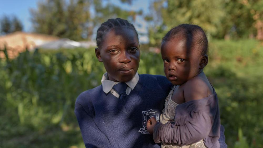 """Evelina,"" 17, with her 3-year-old daughter ""Hope,"" in Migori county, western Kenya. Evelina is in Form 2, the second year of lower secondary school."