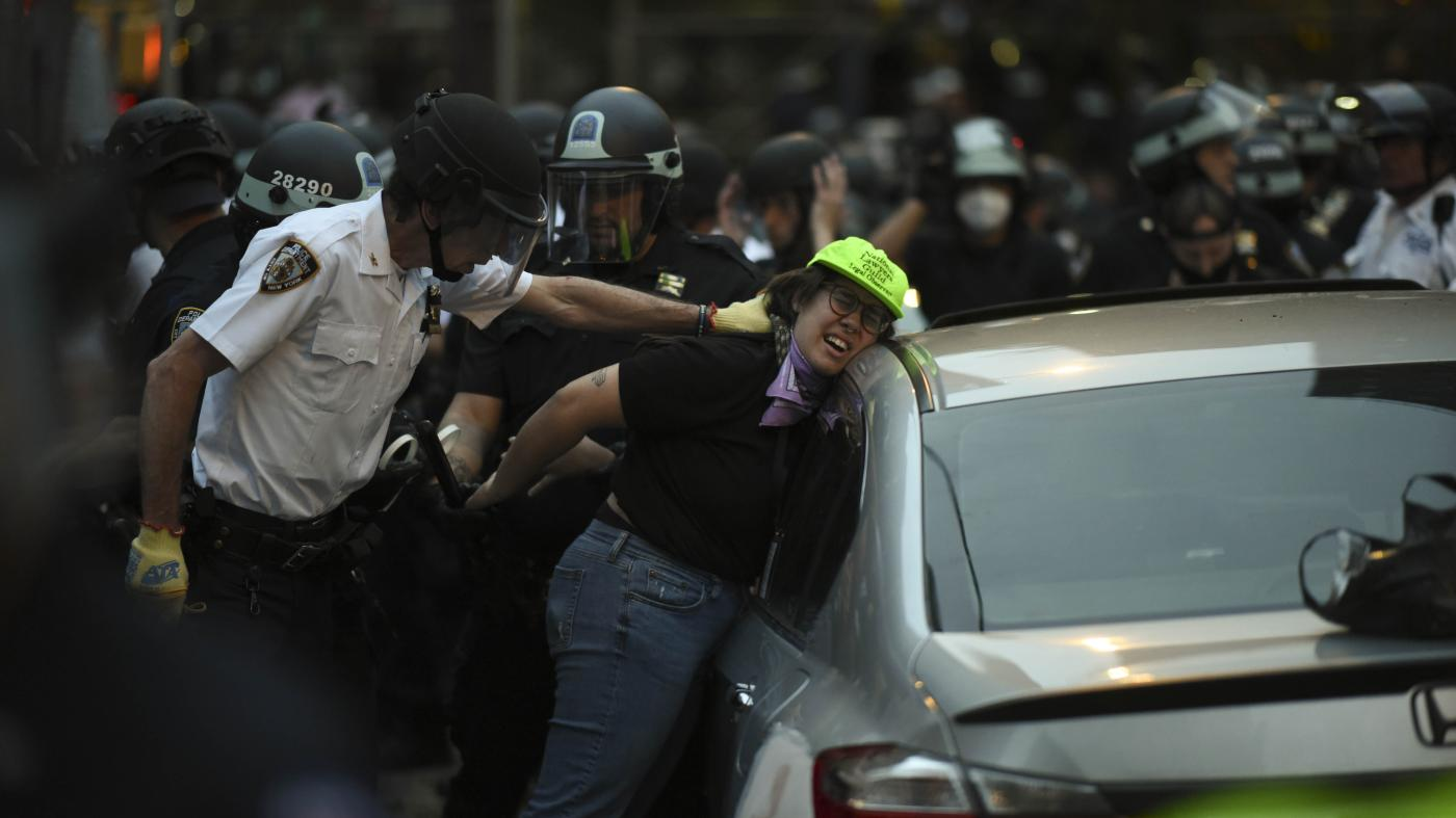 Police push a woman in a green hat against a car and handcuff her