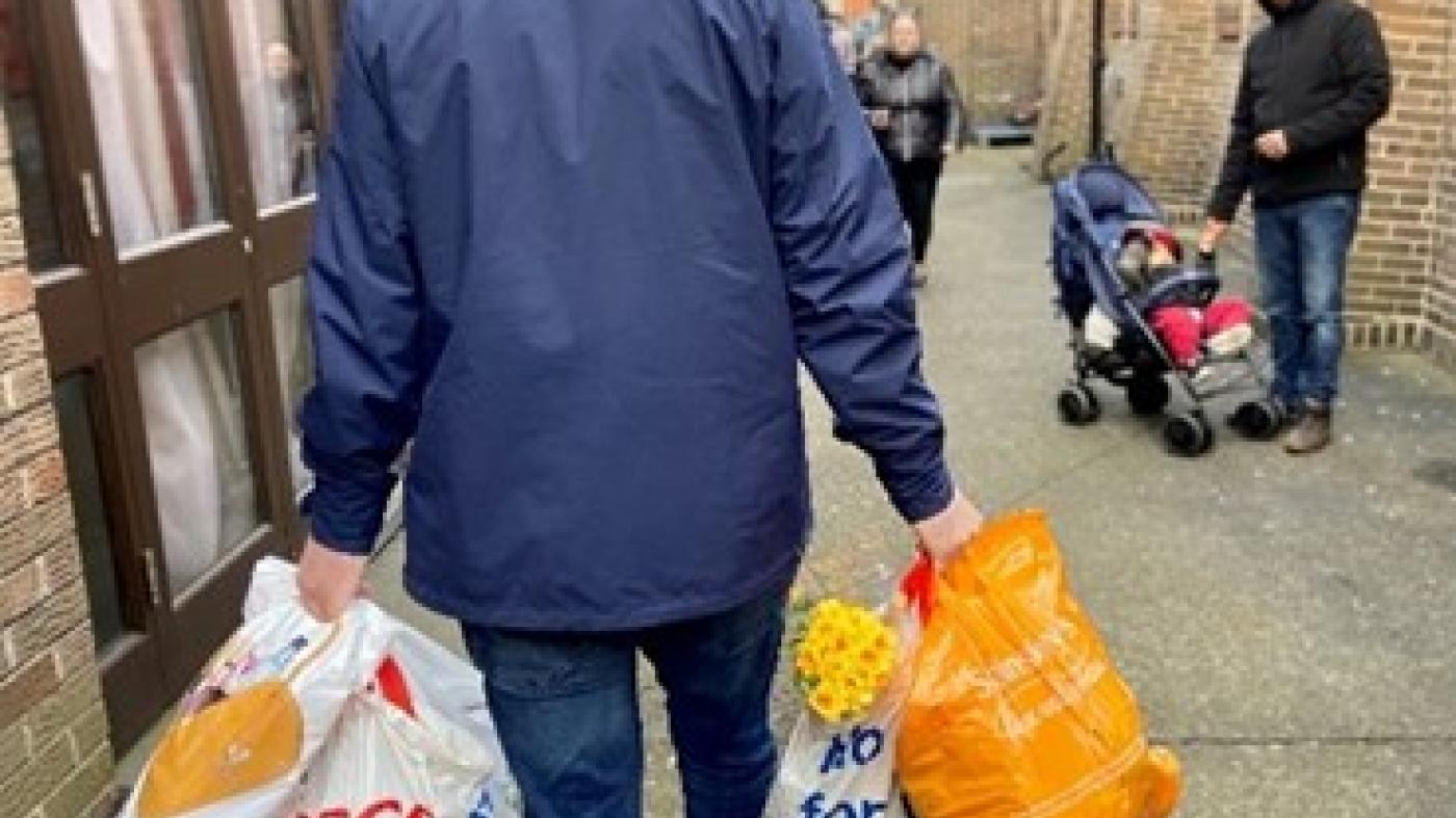 A man in a coat walks down a street carrying grocery bags