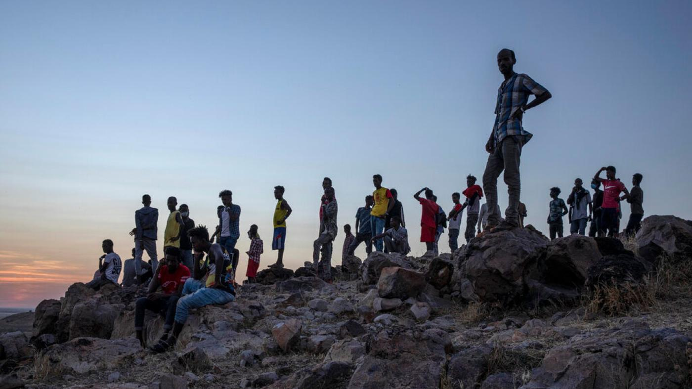 Tigrayans who fled the conflict in Ethiopia's Tigray region stand on a hilltop overlooking Umm Rakouba refugee camp in Qadarif, eastern Sudan, November 26, 2020