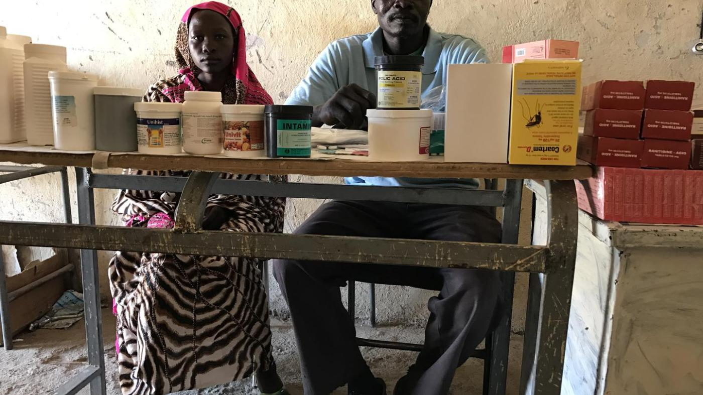 Mukuma Hamad, a volunteer health worker (L), and James Atai, a nurse, sit at a table displaying almost the total stock of basic medicines in the only health clinic in Hadara village, rebel-controlled Southern Kordofan.