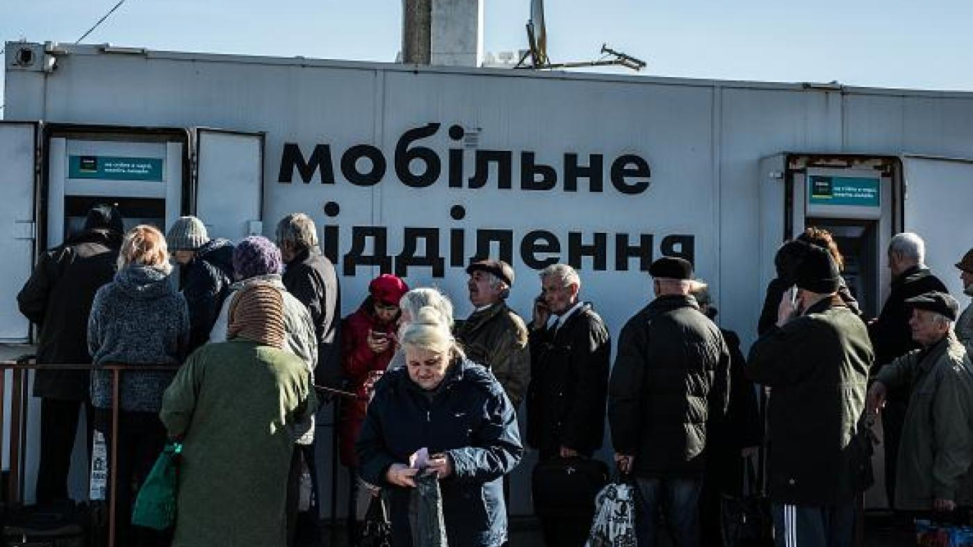 Older people lining up at bank machines in government-controlled areas of Ukraine.