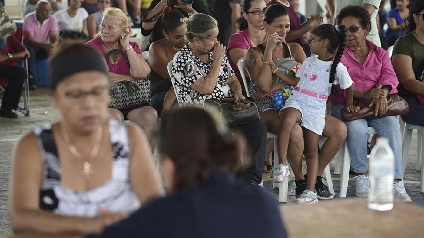 People wait at the Jose de Diego Elementary School to file FEMA forms for federal aid in the aftermath of Hurricane Maria in Las Piedras, Puerto Rico
