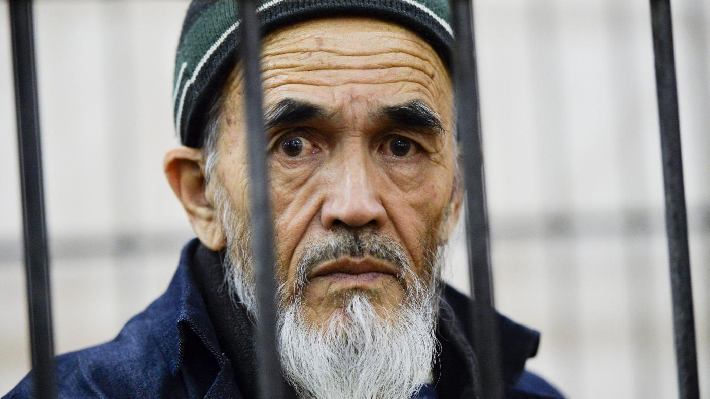 Ethnic Uzbek journalist Azimzhan Askarov, who was arbitrarily arrested, tortured, convicted after an unfair trial and jailed for life looks through metal bars during hearings at the Bishkek regional court, Kyrgyzstan.