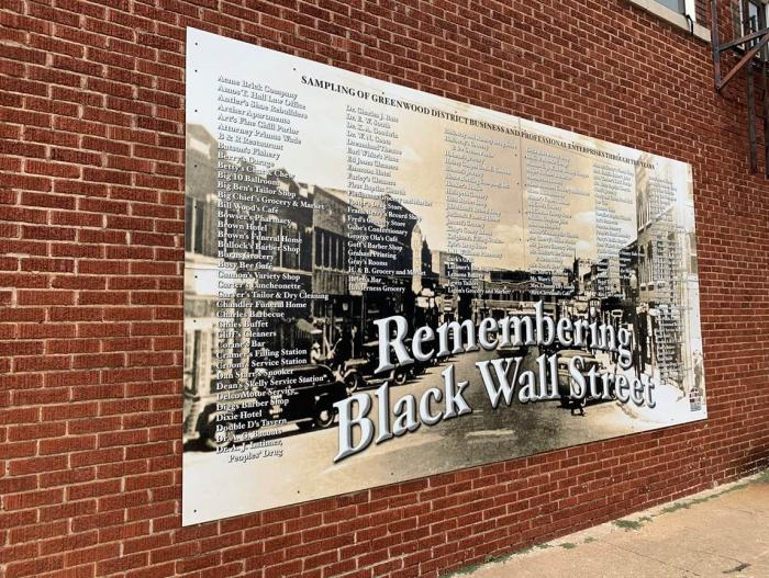 "A sign commemorating the business and professional enterprises a part of the prosperous black entrepreneurial mecca, Oklahoma's Greenwood District, aka ""Black Wall Street."""