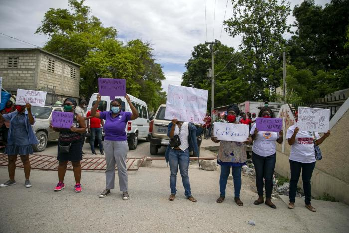 Women hold up signs demanding justice during the hearing of the president of the Fédération Haïtienne De Football (FHF), Yves Jean-Bart, regarding allegations that he abused female athletes at the country's national training center, outside the courthouse in Croix-des-Bouquets, Haiti, Thursday, May 14, 2020.