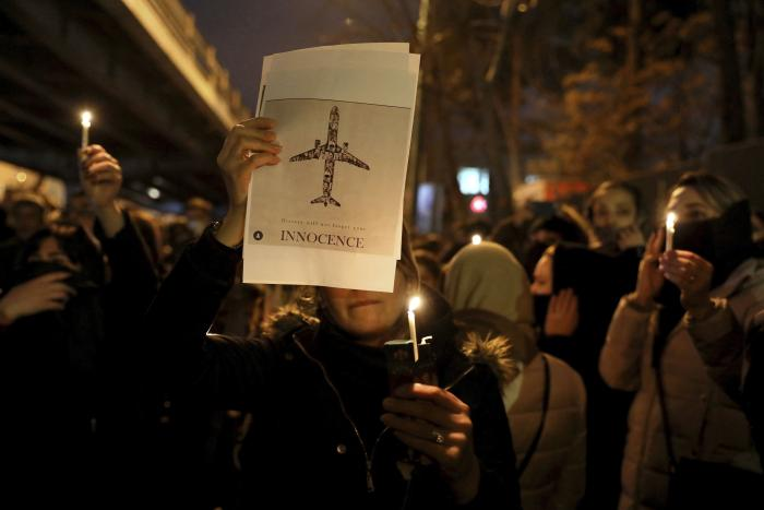 In this January 11, 2020, people gather for a candlelight vigil to remember the victims of the Ukraine plane crash at the gate of Amir Kabir University in Tehran, Iran.