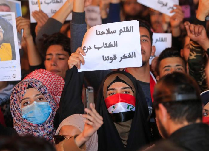 Woman holding up a sign in Arabic