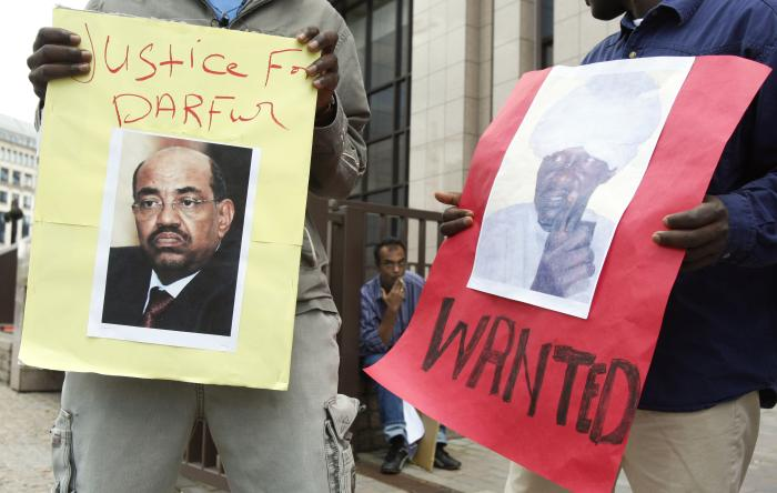 Protesters hold posters of Sudan's then-President Omar Hassan al-Bashir and Janjaweed leader Ali Kosheib (R) outside the European Union Council in Brussels, July 2008.