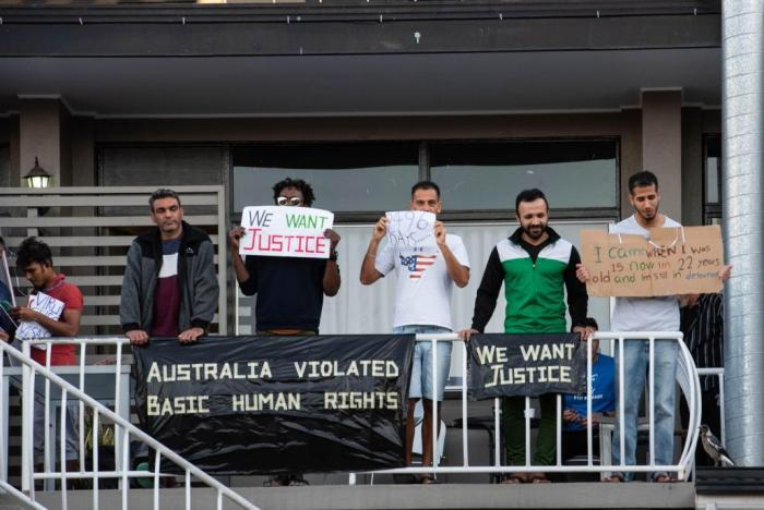 Asylum seekers and refugees hold placards during protest against their detention at Kangaroo Point Hotel in Brisbane, Australia, amid the Covid-19 crisis.