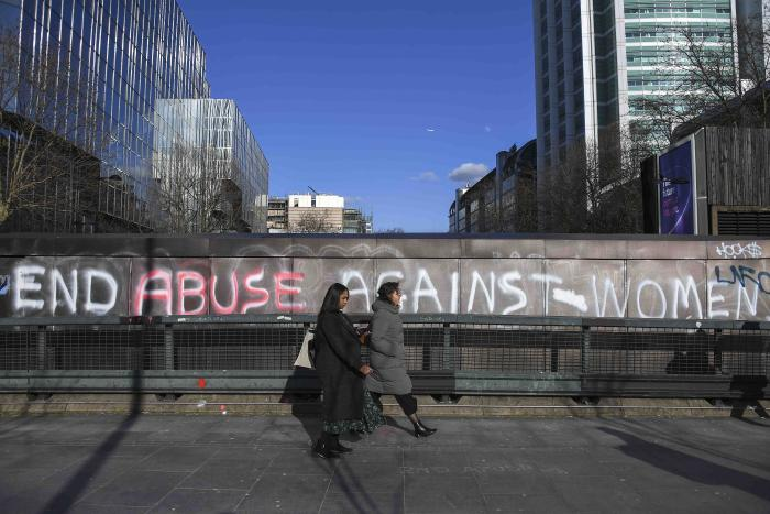 People walk past a graffiti reading 'End abuse against women' on Euston Road, in London, Friday March 6, 2020.