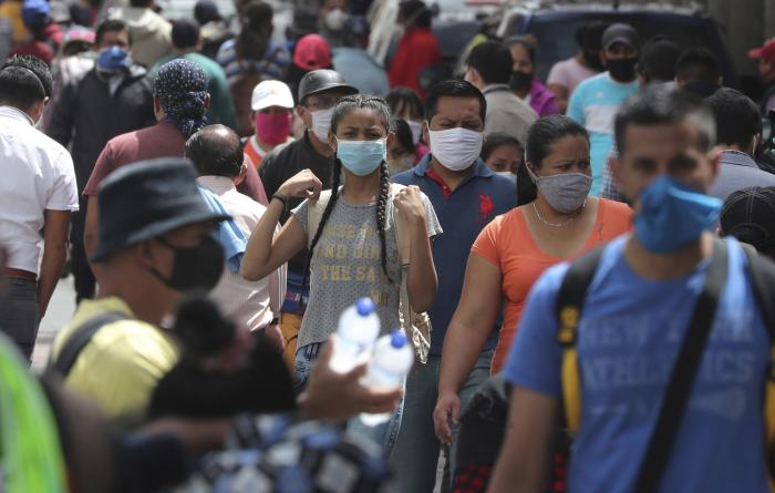 People wearing masks walk downtown amid the new coronavirus pandemic in Quito, Ecuador on Monday, June 29, 2020.
