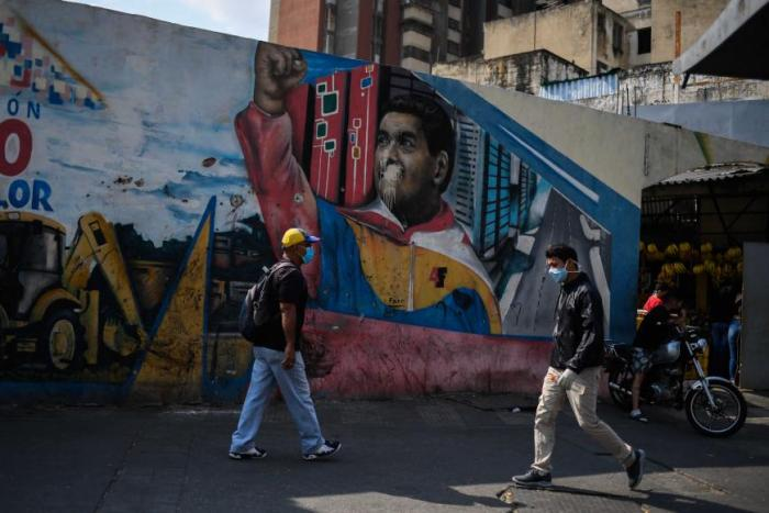 People wearing face masks walk past a mural depicting Venezuelan president Nicolas Maduro in Caracas on April 17, 2020, amid the novel coronavirus (COVID-19) outbreak
