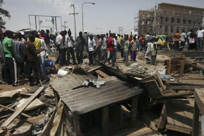 People gathered around the wreckage of a damaged road side tea shop following an explosion in Kaduna, Nigeria Monday, April 9, 2012.