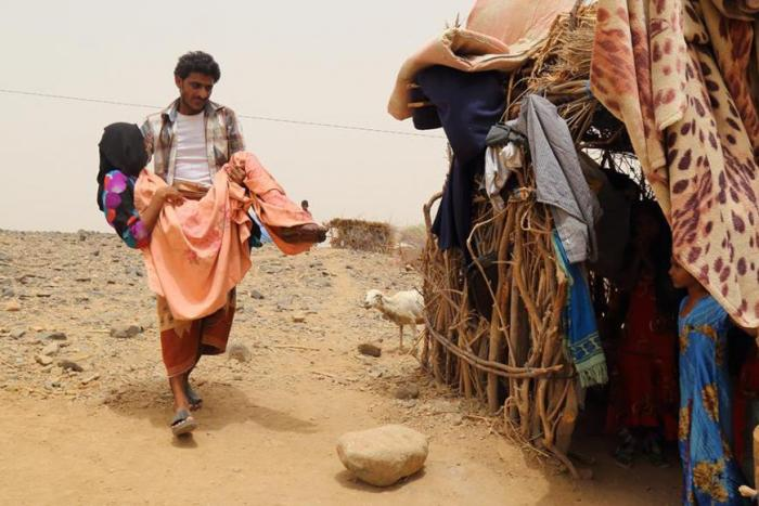 A woman is carried by her brother outside a home in Malus, Yemen.