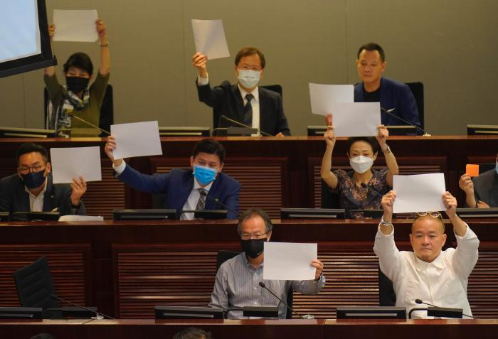 Pro-democracy lawmakers raise white papers to protest during a meeting to discuss the new national security law at the Legislative Council in Hong Kong, July 7, 2020. © 2020 AP Photo/Vincent Yu