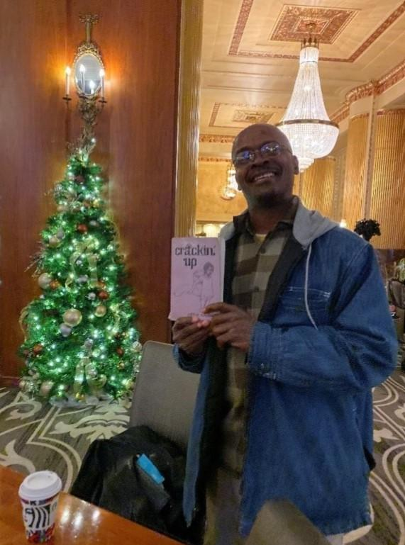 A man poses with a novel in front of a Christmas tree
