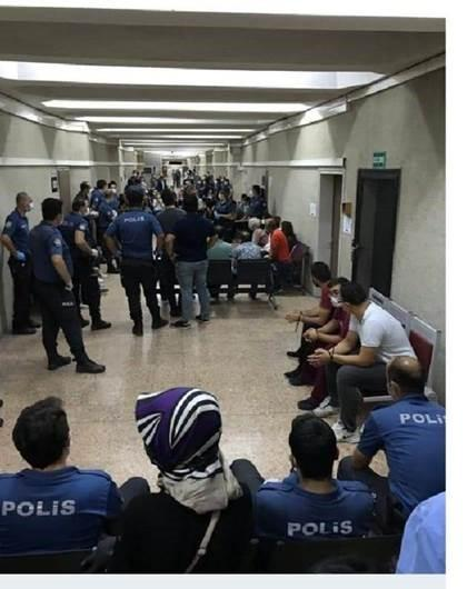 Defense lawyers, arrested in dawn raids on September 11 because they represent persons accused on terrorism charges, are handcuffed as they wait with police in the corridor of the Ankara courthouse, September 14, 2020 © 2020 private