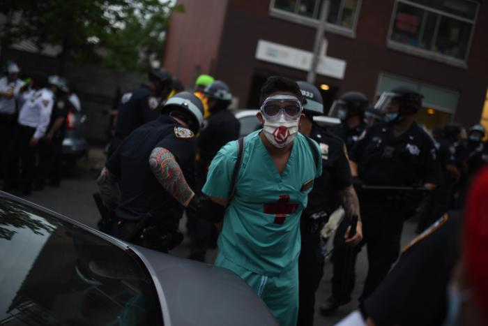 A man in a mask and hospital scrubs is handcuffed by police officers