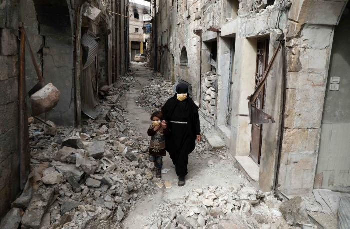 A woman in a black niqab and face mask walks through a deserted street with a child