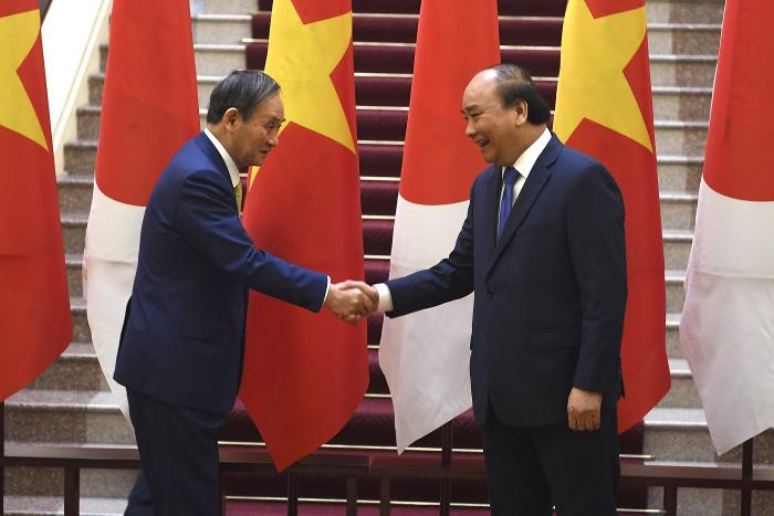 Japan's Prime Minister Yoshihide Suga, left, shakes hands with Vietnam's Prime Minister Nguyen Xuan Phuc after the exchange of documents at the Government Office in Hanoi on Monday, October19, 2020.