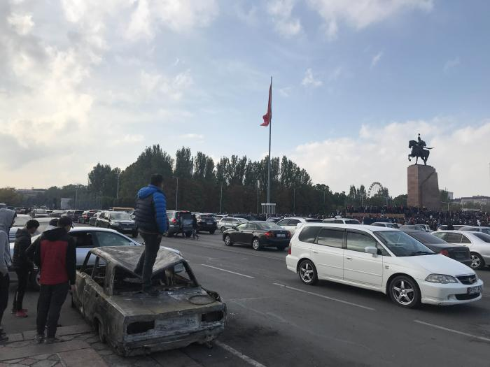 A man stands on a burnt out car following a night of unrest in connection with protests against the October 4 parliamentary vote in Bishkek, Kyrgyzstan.