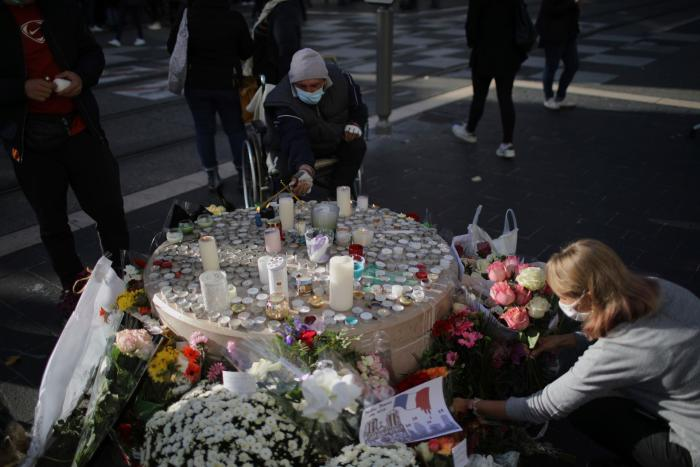 People set flowers at a memorial in front of the Notre Dame church, in Nice, France, October 30, 2020.