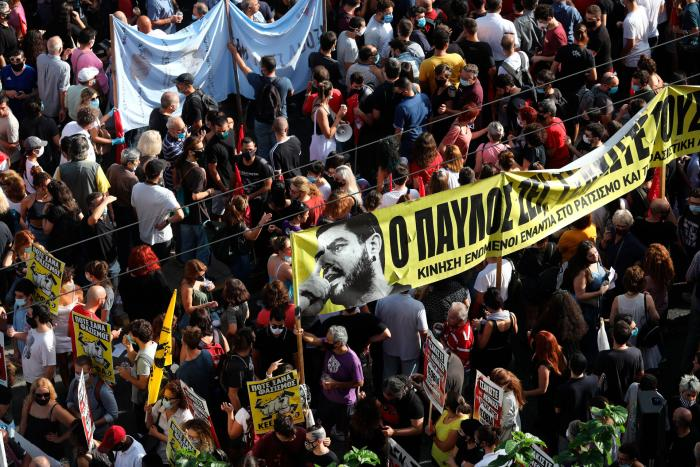 Peopleholding a banner depicting Greek rap singer Pavlos Fyssas, who was stabbed and killed by a supporter of the extreme right Golden Dawn party in 2013, gather for a protest outside a court in Athens, Wednesday, October 7, 2020.