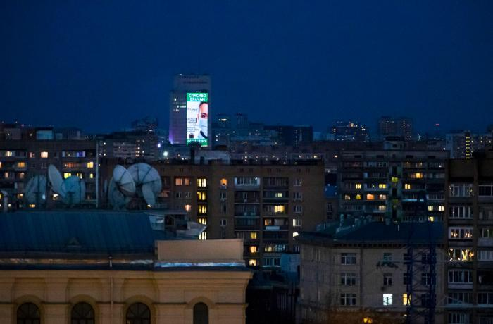 An electronic billboard  is displayed on a office building after sunset in Moscow, Russia, April, 11, 2020.