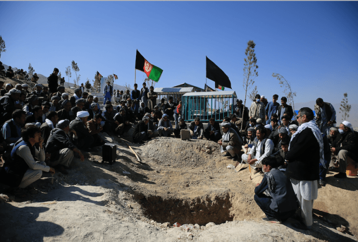Afghan men bury a victim of the suicide attack that targeted a school  in Kabul, Afghanistan, October 25, 2020