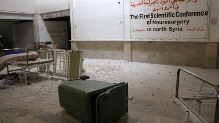 Overturned furniture and rubble in an empty hospital room