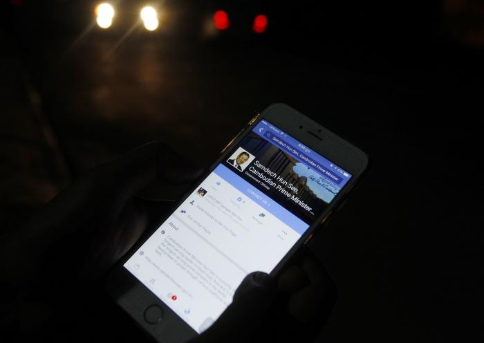A man views Cambodian Prime Minister Hun Sen's Facebook page on his mobile phone in downtown Phnom Penh, Cambodia.