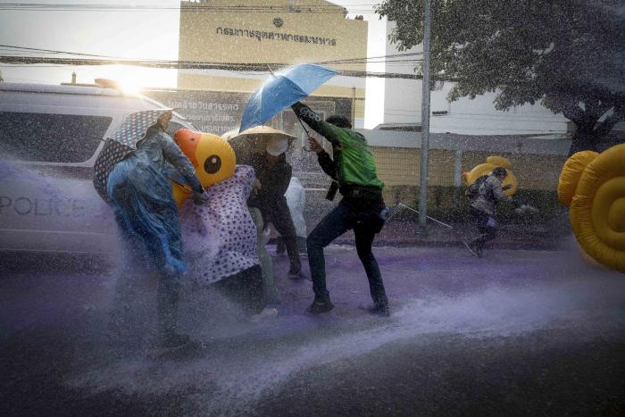 Democracy demonstrators take cover with inflatable ducks and umbrellas as police use water cannons during a protest rally near the parliament in Bangkok, November 17, 2020. © 2020 AP Photo/Wason Wanichakorn