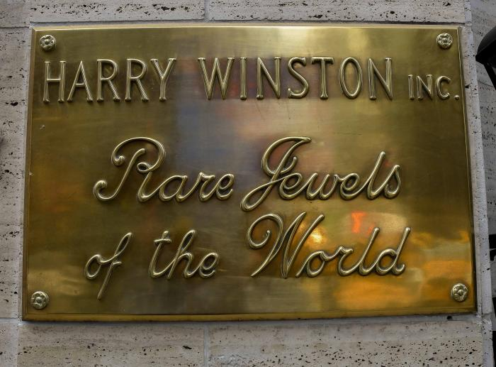 "A gold plaque that reads ""Harry Winston Inc.: Rare Jewels of the World"""