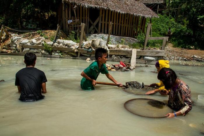 Four kids hold mining tools in a river