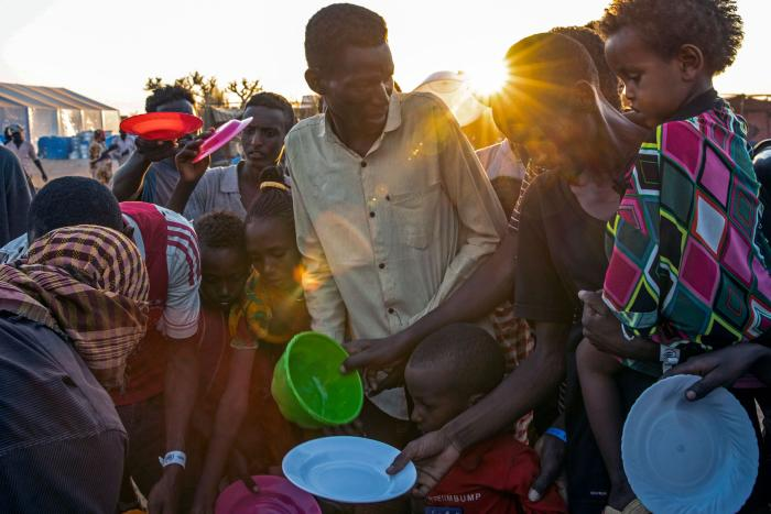 People who fled the conflict in Ethiopia's Tigray region wait for food at Um Raquba refugee camp in al-Gadaref state, eastern Sudan, November 23, 2020.