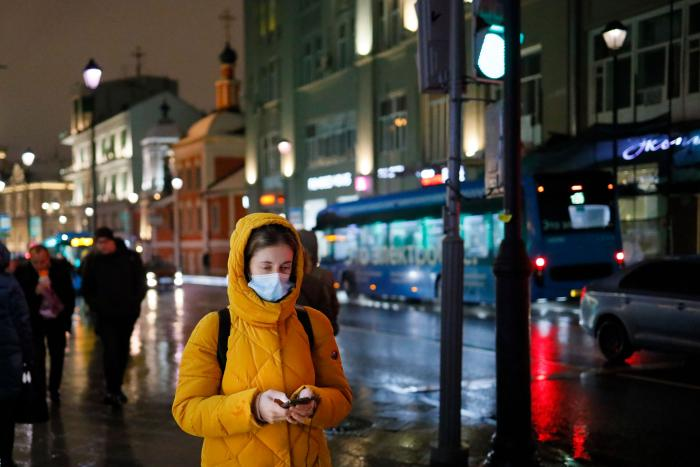 A woman wearing a face mask looks at her smartphone as she walks through a street in Moscow, Russia, November 23, 2020.