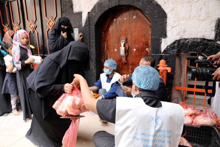 An aid worker gives a food ration to a woman in Sanaa, Yemen, July 19, 2020