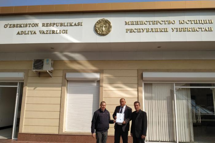 "Azam Farmonov, center, and Dilmurod Saidov, right, after receiving a registration certificate for their NGO ""Huquqi Tayanch"" in front of the Justice Ministry in Tashkent, Uzbekistan."