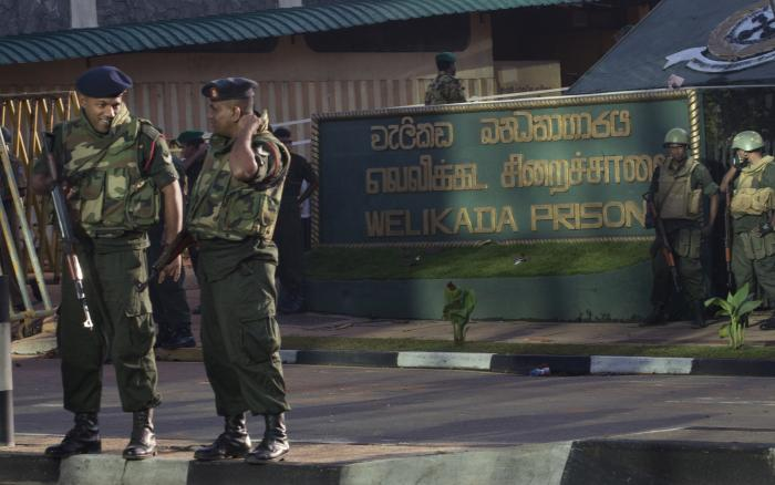 "Armed soldiers stand in front of a building with a sign that reads ""Welikada Prison"""