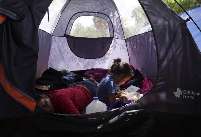 Asylum seeker Yareni, age five, flips through the pages of a book in an encampment where she lives near the Gateway International Bridge in Matamoros, Mexico.