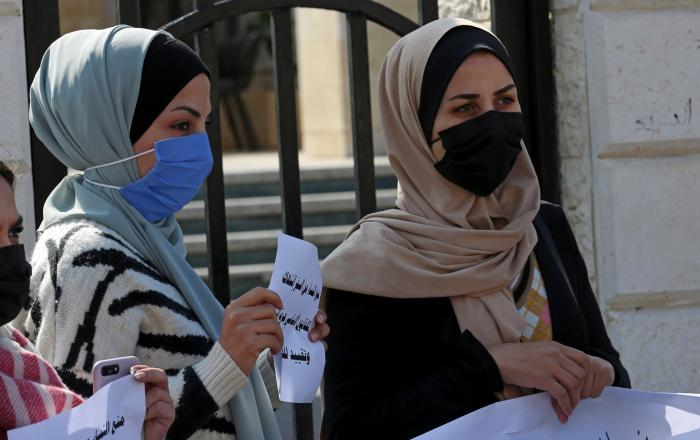 "Women hold signs during a protest against the decision by Gaza's Supreme Judicial Council banning women from movement in and out of the Gaza Strip without the permission of her ""guardian,"" in Gaza City, February 16, 2021."